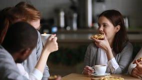 Os colegas diversos tomam a ruptura que comem o café bebendo da pizza apreciam a conversação vídeos de arquivo