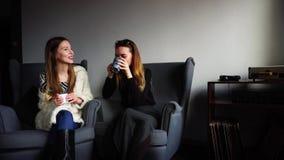 Os colegas fêmeas bonitos falam e riem do copo do chá durante a ruptura do trabalho e sentam-se em poltronas cinzentas no café à  filme