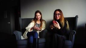 Os colegas fêmeas bonitos usam telefones e bate-papo entre se durante o almoço e sentam-se em poltronas cinzentas em à moda video estoque