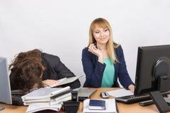 Os colegas fêmeas no escritório, um tiveram adormecido caído em uma pilha dos dobradores, a outro que olha felizmente a tela de m Imagem de Stock