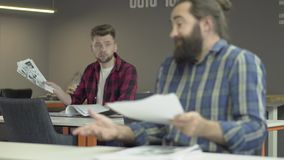 Os colegas leram papéis com planos de trabalho Um trabalhador ou homem de negócios de escritório são indignante no pokachateley e filme