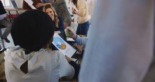 Os colegas multi-étnicos da empresa das vendas trabalham junto com cartas impressas na tabela do escritório Discuss?o saud?vel do video estoque