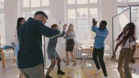 Os colegas multi-étnicos novos felizes da empresa de partida comemoram as realizações que dançam no movimento lento de excita filme
