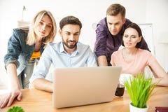 Os colegas novos alegres estão usando o computador para o trabalho Foto de Stock Royalty Free