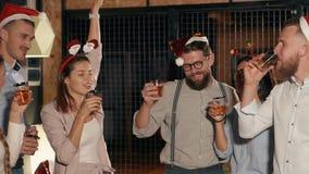 Os colegas novos estão bebendo cocktail no partido incorporado do Natal no escritório vídeos de arquivo