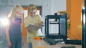 Os colegas olham uma tabuleta ao trabalhar com uma impressora 3D em um laboratório 4K video estoque
