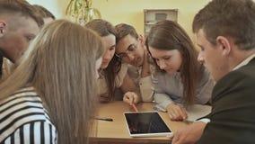 Os colegas sentam-se em torno da mesa e discutem-se a tarefa da escola com a tabuleta Escola do russo filme