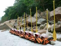 Os colete salva-vidas e os remos alinharam imagens de stock royalty free