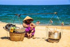 Os comerciantes vendem o alimento local aos turistas em uma praia Fotografia de Stock