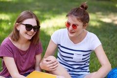 Os companheiros fêmeas positivos têm o divertimento junto, sorriso amplamente quando o recreat no parque, rir do gracejo engraçad fotos de stock royalty free