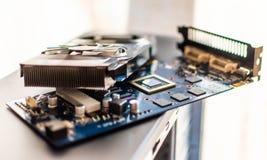 Os componentes de um computador de secretária pessoal uma placa de vídeo desmontada da placa com um mais fresco encontram-se no e imagem de stock royalty free