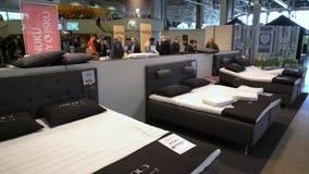 Os compradores estão experimentando uma cama ortopédica nova com controlo a distância video estoque