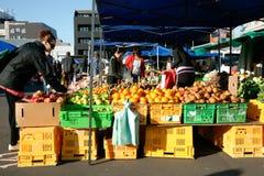 Os compradores selecionam legumes frescos no mercado. fotografia de stock