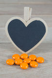 Os comprimidos alaranjados com coração vazio dão forma ao quadro-negro no backgrou de madeira foto de stock royalty free