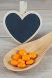 Os comprimidos alaranjados na colher de madeira com coração vazio dão forma ao quadro-negro fotografia de stock