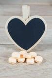 Os comprimidos alaranjados pasteis com coração vazio dão forma ao quadro-negro na madeira b imagem de stock royalty free
