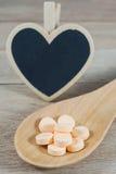 Os comprimidos alaranjados pasteis na colher de madeira com coração vazio dão forma ao preto foto de stock royalty free