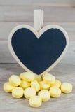 Os comprimidos amarelos com coração vazio dão forma ao quadro-negro no backgrou de madeira fotos de stock