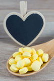 Os comprimidos amarelos na colher de madeira com coração vazio dão forma ao quadro-negro fotografia de stock