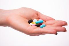 Os comprimidos, as tabuletas, as vitaminas e as drogas empilham nas mãos da mulher Fotos de Stock