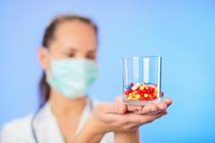 Os comprimidos, as tabuletas e as drogas empilham na mão do doutor imagens de stock