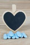 Os comprimidos azuis com coração vazio dão forma ao quadro-negro no fundo de madeira fotos de stock royalty free