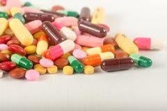 Os comprimidos coloridos salpicam o fundo branco As tabuletas e as drogas diferentes da terapia da mistura do montão da cápsula imagem de stock royalty free