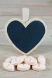 Os comprimidos cor-de-rosa com coração vazio dão forma ao quadro-negro no fundo de madeira imagem de stock