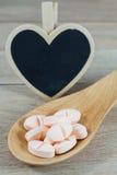Os comprimidos cor-de-rosa na colher de madeira com coração vazio dão forma ao quadro-negro foto de stock royalty free