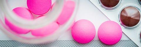 Os comprimidos cor-de-rosa são derramados de um frasco de vidro e as bolhas com tabuletas coloridas são dispersadas em um fundo b imagens de stock