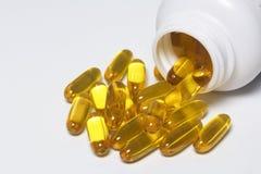 Os comprimidos da cor amarela são derramados em uma superfície branca do frasco plástico foto de stock royalty free