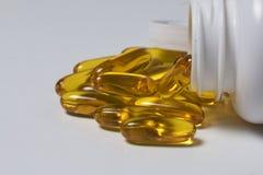 Os comprimidos da cor amarela são derramados em uma superfície branca dos frascos plásticos Vista de acima Imagens de Stock