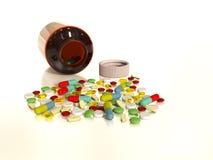 Os comprimidos de Collorful derramaram a garrafa Imagens de Stock Royalty Free