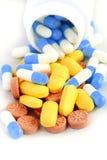 Os comprimidos e as tabuletas coloridos derramaram o frasco Imagem de Stock