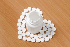 Os comprimidos e a garrafa brancos no plano lustraram a superfície de madeira Comprimidos AR imagens de stock royalty free