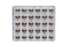 Os comprimidos marrons em um bloco de bolha ilustração stock