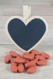 Os comprimidos vermelhos com coração vazio dão forma ao quadro-negro no fundo de madeira imagens de stock
