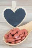 Os comprimidos vermelhos na colher de madeira com coração vazio dão forma ao quadro-negro fotografia de stock royalty free
