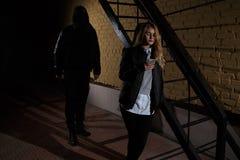 Os conceitos da extorsão dos conceitos do crime um ladrão apontaram sua faca afiada em uma mulher roubar suas coisas valiosas no  fotos de stock royalty free