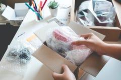 Os conceitos de compra em linha com a caixa aberta fêmea, apresentam algum produto em sua mão fotografia de stock royalty free