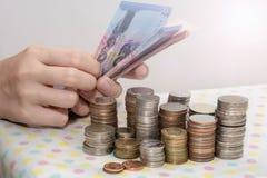 Os conceitos de contabilidade apresentam pela m?o f?mea que conta contas do baht atr?s das pilhas da moeda do dinheiro no branco fotografia de stock