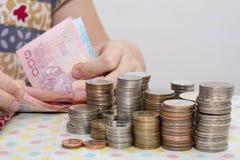 Os conceitos de contabilidade apresentam pela m?o f?mea que conta contas do baht atr?s das pilhas da moeda do dinheiro no branco fotografia de stock royalty free