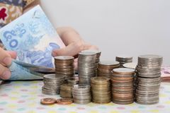 Os conceitos de contabilidade apresentam pela m?o f?mea que conta contas do baht atr?s das pilhas da moeda do dinheiro no branco imagens de stock