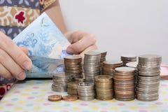 Os conceitos de contabilidade apresentam pela m?o f?mea que conta contas do baht atr?s das pilhas da moeda do dinheiro no branco foto de stock royalty free