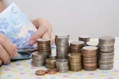 Os conceitos de contabilidade apresentam pela m?o f?mea que conta contas do baht atr?s das pilhas da moeda do dinheiro no branco fotos de stock royalty free