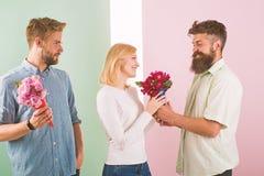 Os concorrentes dos homens com tentativa das flores dos ramalhetes conquistam a menina Sorriso da menina feito sua escolha Concei fotos de stock
