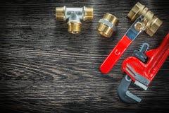 Os conectores da chave de macaco do encanamento molham a válvula no vintage de madeira fotografia de stock