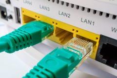 Os conectores verdes para o Internet incluído em um roteador foto de stock