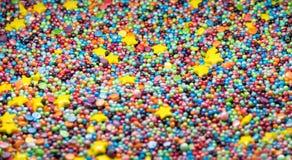 Os confeitos coloridos doces que polvilham a textura com o açúcar amarelo das estrelas polvilham pontos imagem de stock royalty free
