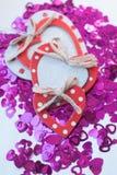 Os confetes na forma dos corações dispersaram na tabela Fotos de Stock